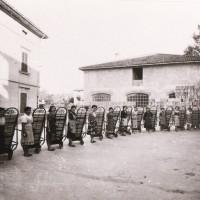 """Questa foto del 1950 ritrae un gruppo di cernitrici impiegate nel magazzino Garagnani di Savignano sul Panaro, detto """"Fabbricone"""". Sui carrelli sono accatastate cassette di frutta"""