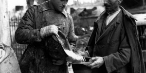 Monghidoro, Appennino bolognese: un ufficiale del Governo militare alleato versa un elmetto pieno di fagioli nel cappello di un civile italiano (2 novembre 1944),  foto in archivio dell'Istituto per la storia e le memorie del '900 Parri Emilia-Romagna.